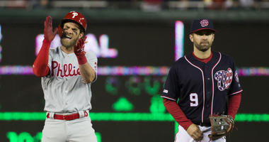 Philadelphia Phillies' Bryce Harper, left, celebrates his RBI hit while on second base with Washington Nationals second baseman Brian Dozier during the sixth inning of a baseball game at Nationals Park, Tuesday, April 2, 2019, in Washington.