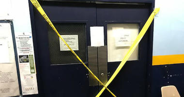 """The double doors of the 39th Police District building's roll call room are branded with a giant """"X"""" made out of yellow police caution tape due to reports of mold inside."""