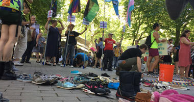 Protesters gathered shoes to represent children who are sleeping in tents without parents due to the Trump administration's separation policy.