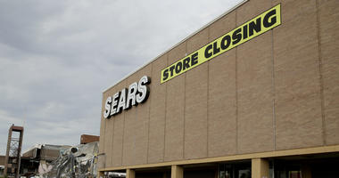 In this July 8, 2017, file photo people walk into a Sears store slated for closing that is next to a mall that is being torn down in Overland Park, Kan