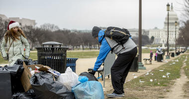The Capitol building is visible as a man who declined to give his name picks up garbage and stacks it near a trash can during a partial government shutdown on the National Mall in Washington, Tuesday, Dec. 25, 2018.