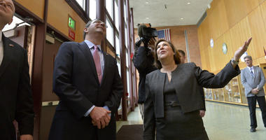 Superintendent of the Abington School District Amy Sichel gestures upward toward a group of students standing on a balcony as Secretary of Defense Ash Carter arrives at Abington Senior High School to visit his alma mater March 30, 2015.