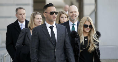 """Michael """"The Situation"""" Sorrentino walks with his fiancee Lauren Pesce while leaving the federal courthouse after a hearing in Newark, N.J., on Jan. 19, 2018."""
