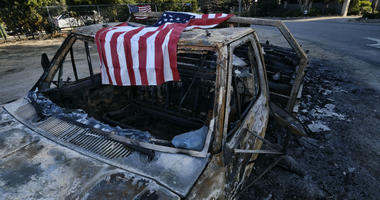 An American flag is draped over the charred remains of an old pickup truck entering Point Dume along the pacific coast highway in Malibu, Calif., on Sunday Nov. 11, 2018.