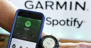 In this Oct. 3, 2018, file photo a Garmin International employee shows the new Spotify app on his smartphone integrated with his Garmin fenix 5 Plus watch during a presentation in New York. Spotify reports financial results Wednesday, Feb. 6, 2019.