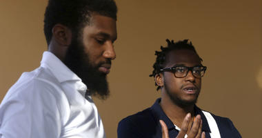 Rashon Nelson, left, listens as and Donte Robinson, right, addresses a reporter's question during an interview with The Associated Press in Philadelphia.