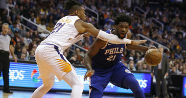 Philadelphia 76ers center Joel Embiid (21) gets fouled by Phoenix Suns forward Richaun Holmes in the second half during an NBA basketball game, Wednesday, Jan. 2, 2019, in Phoenix. The 76ers defeated the Suns 132-127.
