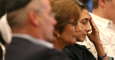 """Dan Gelber, left, sister Judy Gelber and wife Joan Silverstein close their eyes in prayer as members of the Beth Sholom synagogue in Miami Beach, Fla. gathered on Sunday, Oct. 28, 2018 for a """"Time to Grieve."""""""