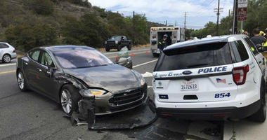 a Tesla sedan, left, in autopilot mode that crashed into a parked police cruiser