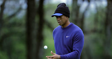Tiger Woods flips his ball as he walks along the ninth green during a practice round for the PGA Championship golf tournament, Monday, May 13, 2019, in Farmingdale, N.Y.