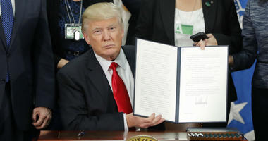 President Donald Trump holds up an executive order for border security and immigration enforcement improvements after signing the order during a visit to the Homeland Security Department headquarters in Washington, on Jan. 25, 2017.