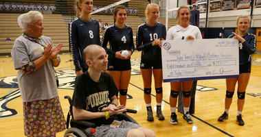 In this Tuesday, Sept. 4, 2018, photo, Central Catholic players present Tyler Trent, foreground, with a check to benefit Riley Children's Hospital before meeting Lafayette Jeff in a high school volleyball game, in Lafayette, Ind.