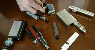 In this April 10, 2018, file photo, a high school principal displays vaping devices that were confiscated from students in such places as restrooms or hallways at the school in Massachusetts.