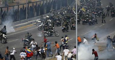 Opponents to Venezuela's President Nicolas Maduro confront loyalist Bolivarian National Guard troops firing tear gas at them, outside La Carlota military airbase in Caracas, Venezuela, Tuesday, April 30, 2019.