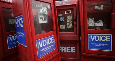 In this Nov. 27, 2013 photo, plastic newspaper boxes for The Village Voice stand along a Manhattan sidewalk in New York.