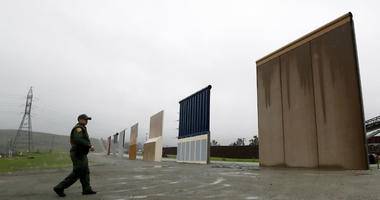 In this Feb. 5, 2019 file photo a Border Patrol agent walks towards prototypes for a border wall in San Diego.