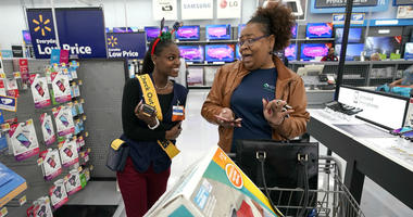 """Walmart associate Shanay Bishop, left, checks out customer Carolyn Sarpy on the sales floor as part of the """"Check Out With Me"""" program at a Walmart Supercenter in Houston."""