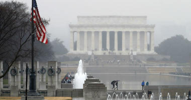 With the Lincoln Memorial in the background, an American flag at the WWII Memorial flies at half-staff, Saturday, Dec. 1, 2018, in Washington.