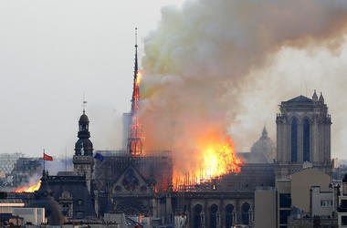 Fames rise from Notre Dame cathedral as it burns in Paris, Monday, April 15, 2019. Massive plumes of yellow brown smoke is filling the air above Notre Dame Cathedral and ash is falling on tourists and others around the island that marks the center of Pari