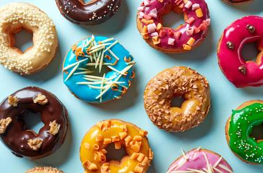 A plate with donuts in a variety of colors and flavors