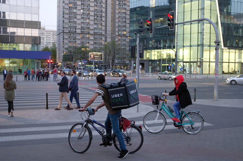 An Uber Eats meal delivery bicyclist arrives at an intersection in the city center on April 18, 2018 in Warsaw, Poland. Uber Eats is the biggest meal delivery service in the USA and is expanding aggressively internationally. (Photo by Sean Gallup/Getty I