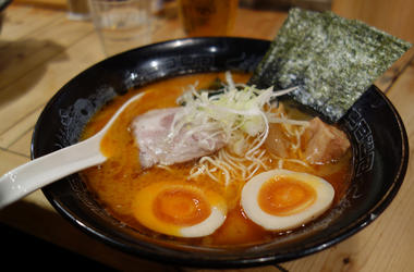 Candid shot of authentic Japanese ramen noodles in black bowl - Real, unposed shot of authentic ramen noodles in a black bowl, taken at a Japanese Restaurant. Complete with egg, noodles seaweed and ramen spoon in a tasty broth.