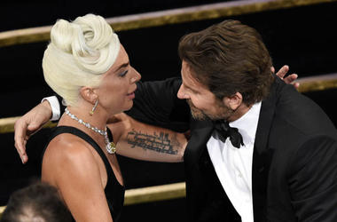 """Bradley Cooper, right, congratulates Lady Gaga in the audience after she is announced winner for best original song for """"Shallow"""" from """"A Star Is Born"""""""