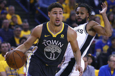 Golden State Warriors' Klay Thompson (11) drives the ball away from San Antonio Spurs' Patty Mills, right, during the first quarter in Game 2 of a first-round NBA basketball playoff series Monday, April 16, 2018, in Oakland, Calif. (AP Photo/Ben Margot)