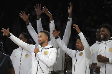 Golden State Warriors' Stephen Curry, left, speaks to fans during an awards ceremony to recognize the team's NBA championship prior to a basketball game against the Oklahoma City Thunder, Tuesday, Oct. 16, 2018, in Oakland, Calif. (AP Photo/Ben Margot)