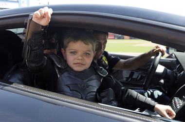 In this file photo from Tuesday, April 8, 2014, Miles Scott, dressed as Batkid, gestures as he sits in the Batmobile after throwing the ceremonial first pitch before a baseball game between the San Francisco Giants and the Arizona Diamondbacks in San Fran