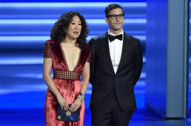 In this Sept. 17, 2018 file photo, Sandra Oh, left, and Andy Samberg present an award at the 70th Primetime Emmy Awards in Los Angeles. Oh and Samberg will share host duties at next month's Golden Globe ceremony. (Photo by Chris Pizzello/Invision/AP, File