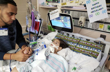 This recent but undated photo, released Monday, Dec. 17, 2018 by the Council on American-Islamic Relations in Sacramento, Calif., shows Ali Hassan with his dying 2-year-old son Abdullah in a Sacramento hospital. The boy's Yemeni mother, blocked by the Tru