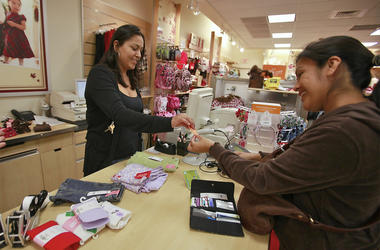 In this Monday, Oct. 4, 2010, file photo, Susi Ortiz, right, buys children's clothing at the Gymboree store at the Westside Pavilion Shopping Center in Los Angeles. Children's clothing retailer Gymboree has filed bankruptcy protection for a second time in