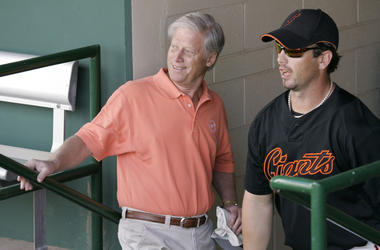 This March 1, 2008, file photo shows San Francisco Giants managing general partner Peter Magowan, left, visiting with center fielder Aaron Rowand, right, in the dugout prior to their spring training baseball game against the Oakland Athletics in Scottsdal
