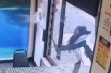 "In this Jan. 15, 2019 image taken from surveillance video, a woman smashes the windows of ""Back Home Restaurant"" in the Bronx borough of New York. Police say that she became upset after ordering a patty and was told that the restaurant had run out of them"