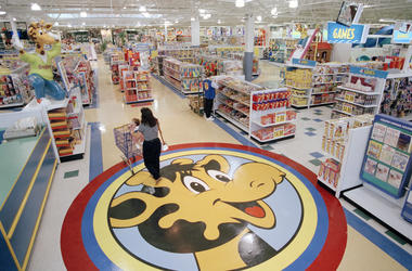 In this July 30, 1996, file photo, a woman pushes a shopping cart over a graphic of Toys R Us mascot Geoffrey the giraffe at the Toys R Us store in Raritan, N.J. Richard Barry, a former Toys R Us executive and now CEO of the new company called Tru Kids In