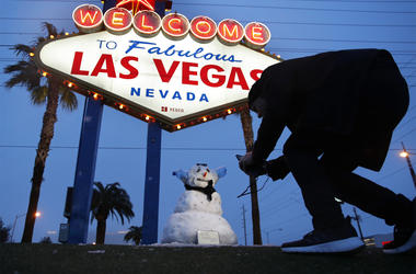 "A man, who declined to give his name, takes a picture of a small snowman at the ""Welcome to Fabulous Las Vegas"" sign along the Las Vegas Strip, Thursday, Feb. 21, 2019, in Las Vegas. (AP Photo/John Locher)"
