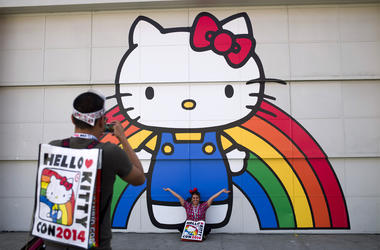 In this Oct. 30, 2014, file photo, Keith Nunez, left, takes pictures of his wife, Carolina, at the first-ever Hello Kitty fan convention, Hello Kitty Con, at the Geffen Contemporary at MOCA in Los Angeles. (AP Photo/Jae C. Hong, File)