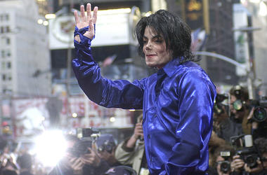 This Nov. 7, 2001 file photo, Michael Jackson waves to crowds gathered to see him at his first ever in-store appearance in New York. (AP Photo/Suzanne Plunkett)