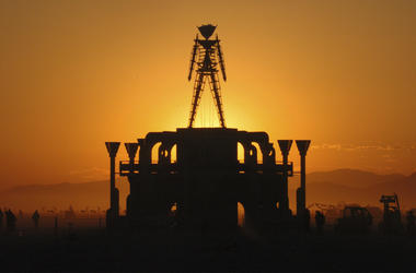 In this Sept. 2, 2006 file photo, The Man, a stick figured symbol of the Burning Man art festival, is silhouetted against a morning sunrise in Nevada's Black Rock Desert. (AP Photo/Ron Lewis, File)