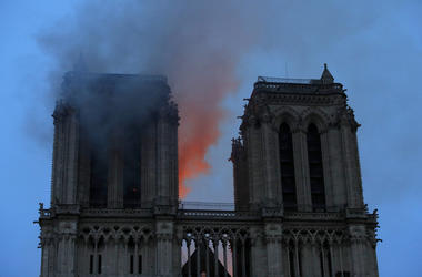 Smoke and flames fill the sky as a fire burns at the Notre Dame Cathedral during the visit by French President Emmanuel Macron in Paris, Monday, April 15, 2019. (Philippe Wojazer/Pool via AP)