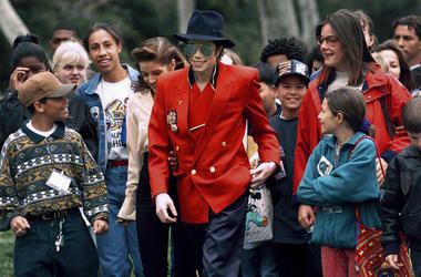 In this April 18, 1995, file photo, pop star Michael Jackson and Lisa Marie Presley, behind him at left, walk with children that were invited guests at his Neverland Ranch home in Santa Ynez, California. (Photo credit: AP Photo/Mark J. Terrill, File)