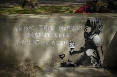 Dappled shade from a tree is cast over a new piece of street art that people noticed for the first time last night and is believed to be by street artist Banksy on a wall where Extinction Rebellion climate protesters had set up a camp in Marble Arch, Lond