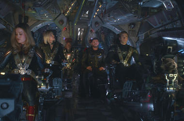 """This image released by Disney shows, from left, Brie Larson, Scarlett Johansson, Don Cheadle, Chris Hemsworth, Chris Evans and the character Rocket, voiced by Bradley Cooper, in a scene from """"Avengers: Endgame."""" (Disney/Marvel Studios via AP)"""
