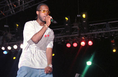 """In this April 12, 1997, file photo, Prakazrel """"Pras"""" Michel, part of the group the Fugees, sings on stage during a concert in Port-au-Prince, Haiti. (AP Photo/Daniel Morel, File)"""