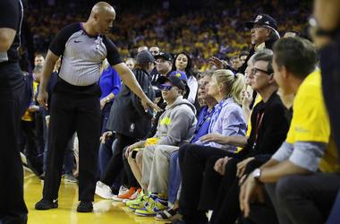 Referee Marc Davis gestures toward Golden State Warriors investor Mark Stevens