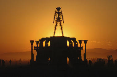 """In this Sept. 2, 2006 file photo, """"The Man,"""" a stick figured symbol of the Burning Man art festival, is silhouetted against a morning sunrise in Nevada's Black Rock Desert. (AP Photo/Ron Lewis, File)"""