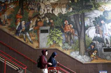 In this photo taken April 3, 2019, a pair of students walk past a historic mural that includes slaves and a dead Native American at George Washington High School in San Francisco. (Yalonda M. James/San Francisco Chronicle via AP)