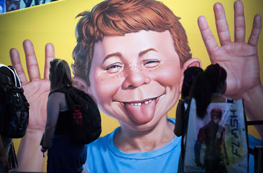 In this July 20, 2017 file photo the face of Alfred E. Neuman is framed by attendees at the DC booth during the first day of Comic-Con International at the San Diego Convention Center in San Diego, California. (Kevin Sullivan/The Orange County Register vi