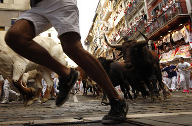 Revellers run next to fighting bulls from Cebada Gago ranch, during the running of the bulls at the San Fermin Festival, in Pamplona, northern Spain, Monday, July 8, 2019. Revellers from around the world flock to Pamplona every year to take part in the ei